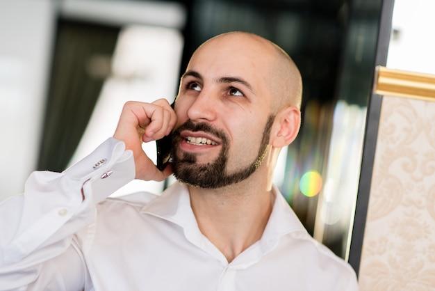 Жестокий лысый мужчина разговаривает по телефону.