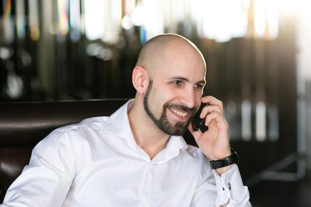 Брутальный лысый мужчина разговаривает по телефону.
