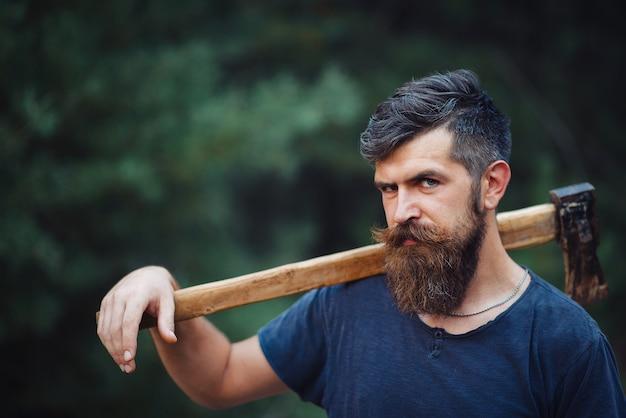 肩に斧を持った暗いtシャツを着た長いあごひげと口ひげを持つ木工職人の残忍なあごひげを生やした男