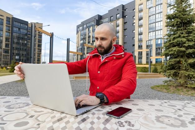 赤いジャケットを着たあごひげを生やした残忍な男が通りのコンピューターで働いています。オンラインでの雇用の概念