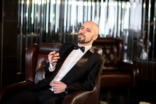 Брутальный мужчина в фрак пальто курит сигару.