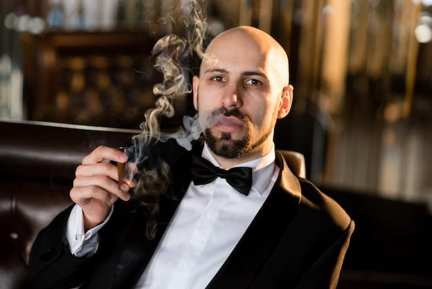Брутальный мужчина в фраке курит сигару