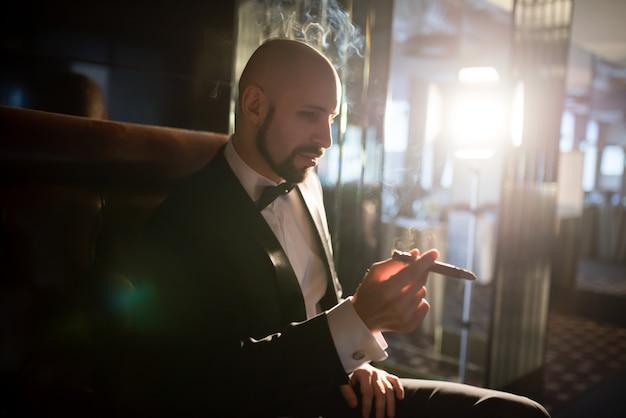 Брутальный мужчина в фраке курит сигару.