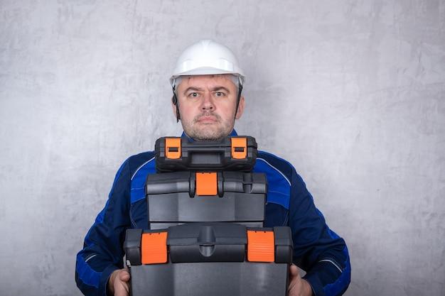 Брутальный мужчина в рабочей форме и белом шлеме держит в руках ящики с инструментами. изолированное изображение на сером фоне