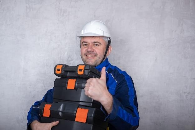 Брутальный мужчина в рабочей форме и белом шлеме держит в руках ящики с инструментами и показывает жест вроде. изолированное изображение на сером фоне