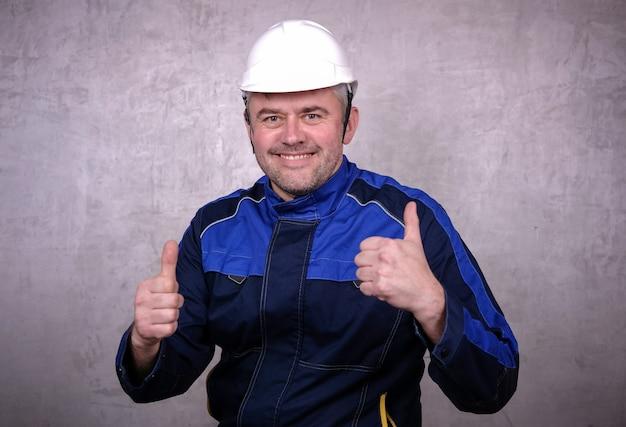 Брутальный мужчина средних лет в черной куртке и белом шлеме с улыбкой показывает жестом два больших пальца вверх. счастливый ремонтник на сером фоне