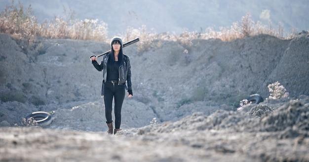 残忍な女性が野球のバットを持って荒れ地を歩く。