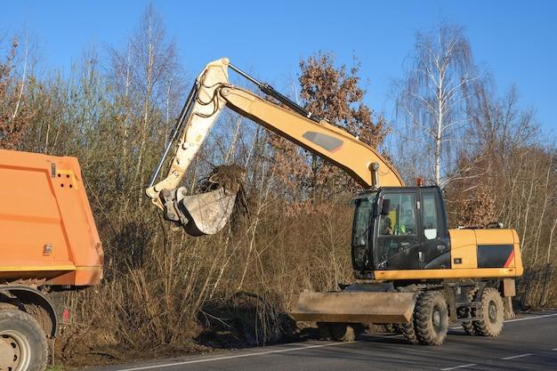 Ковшовый экскаватор расчищает обочину. дорожные работы. прокладка новой дороги. погрузка экскаваторной глины и камней
