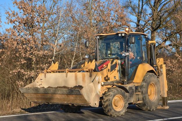 バケツの掘削機が道端を掃除します。道路工事。新しい道を築く。掘削機の粘土と石の読み込み