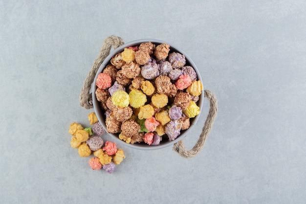 甘い色とりどりのポップコーンがいっぱい入ったバケツ。