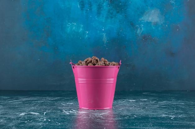 青い背景に、トウモロコシの指輪のバケツ。高品質の写真