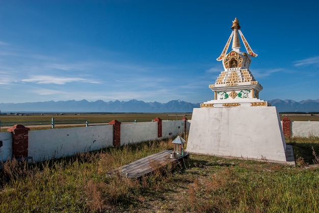 Буддийская тибетская ступа стоит в поле на фоне голубого неба.