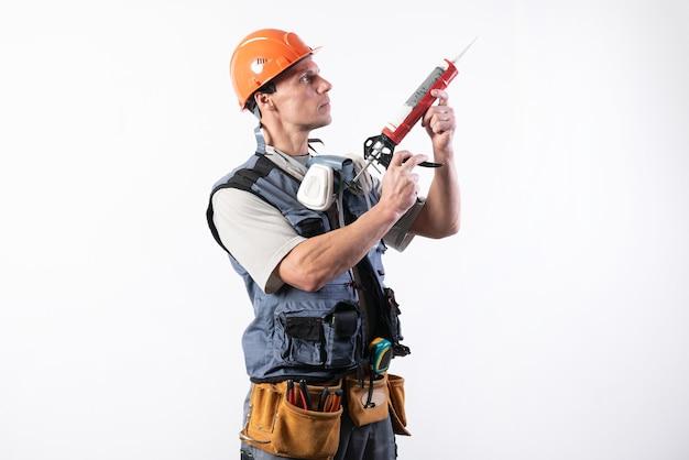 헬멧을 쓴 빌더, 장착 총에 실리콘이 들어 있습니다. 손에 쥐고 있습니다. 밝은 배경에. 어떤 목적을 위해.