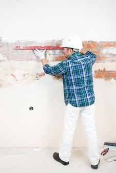 보호 헬멧의 빌더가 집 수리 중에 건물 수준의 평평한 벽돌 벽을 확인합니다.