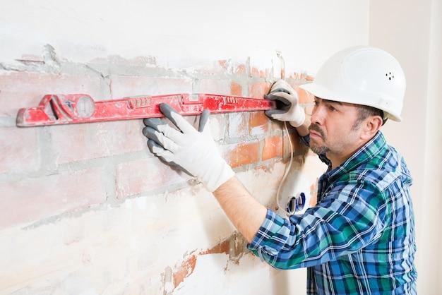 안전 헬멧의 빌더가 집을 수리하는 동안 건물 수준이있는 평평한 벽돌 벽을 확인합니다.