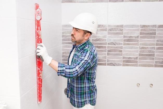 안전모를 쓴 빌더가 리노베이션 중에 욕실 타일의 균일 성을 확인합니다.