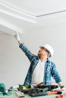 수리하는 동안 도구가있는 안전 헬멧의 건축업자가 천장을 가리 킵니다.