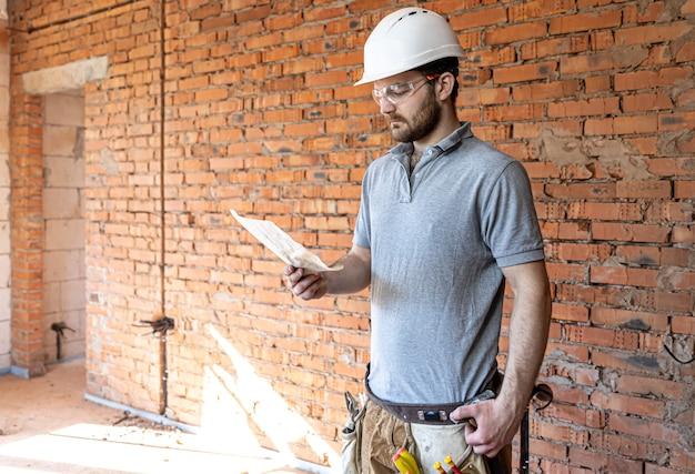 Строитель в спецодежде рассматривает строительный чертеж на стройке.