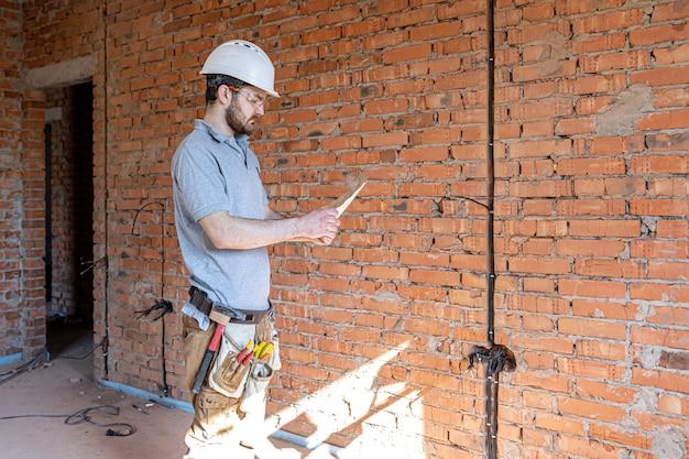 Строитель в спецодежде рассматривает строительный чертеж на строительной площадке