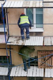 ビルダーが古い家を改築するために木製の足場を設置します
