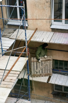 Строитель устанавливает деревянные леса для ремонта старого дома