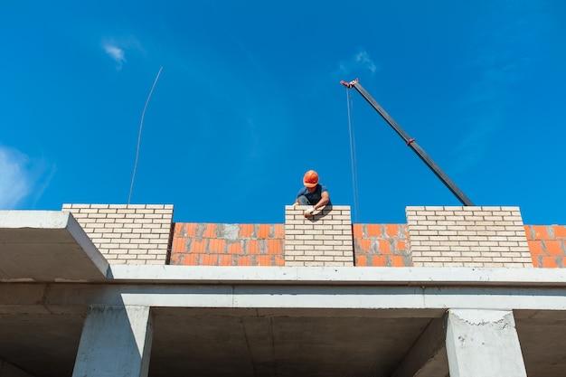 건축업자가 건설 중인 새 집의 벽돌 벽을 깔고 있다