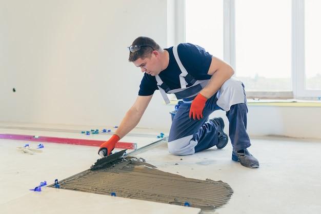 Строитель, укладывающий пол крупной керамической плиткой во время ремонтных работ