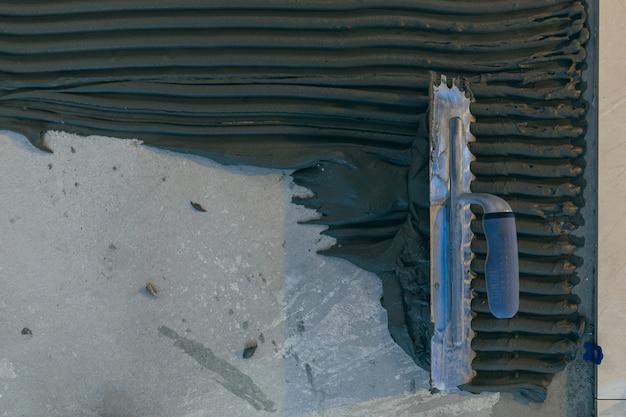 수리 작업 중 대형 세라믹 타일로 바닥을 설치하는 건축업자