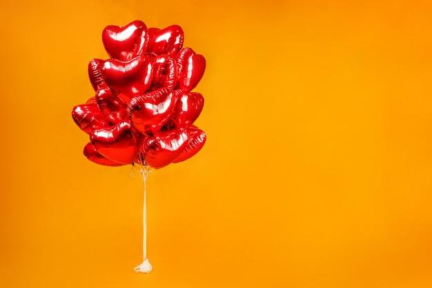 Связка воздушных шаров. красные сердечки на оранжевом фоне.