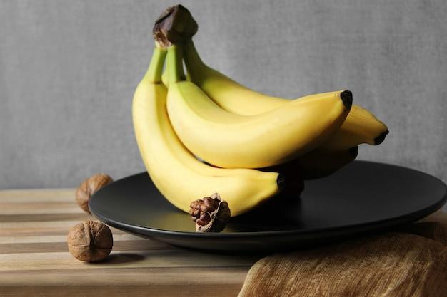 クルミと黒いプレート上のバナナの束