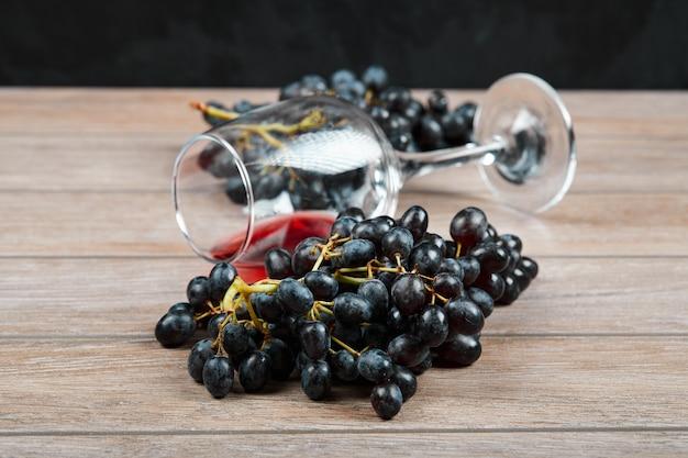黒ブドウの房と木製の背景にワインのグラス。高品質の写真