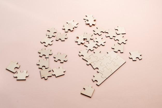 Куча пустых кусочков головоломки на столе, решающая проблему бизнеса