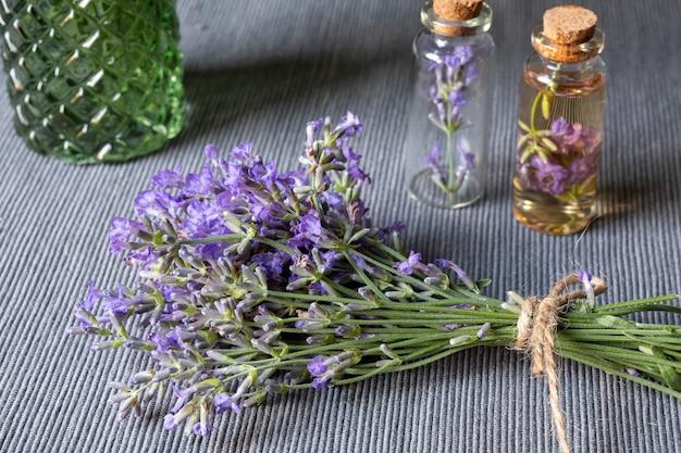 회색 배경에 필수 라벤더 오일과 꽃이 만발한 라벤더와 작은 유리 방울. 식물성 화장품 또는 아로마테라피 개념