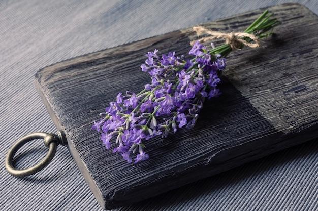 木製のまな板に咲くラベンダーの束。伝統医学、美容またはアロマテラピーの概念