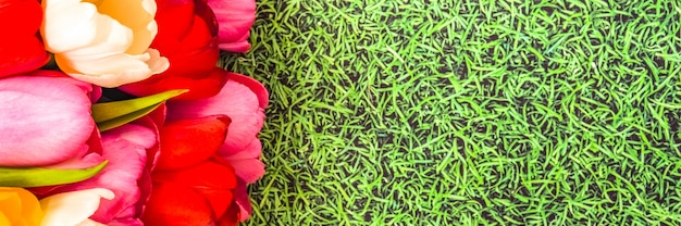 Букет из ярких свежих красочных тюльпанов на фоне травы.