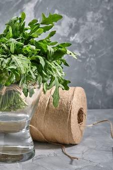 포장 및 배달 재료의 배경에 대해 물이 든 유리 꽃병에 있는 신선한 아루굴라 무리.