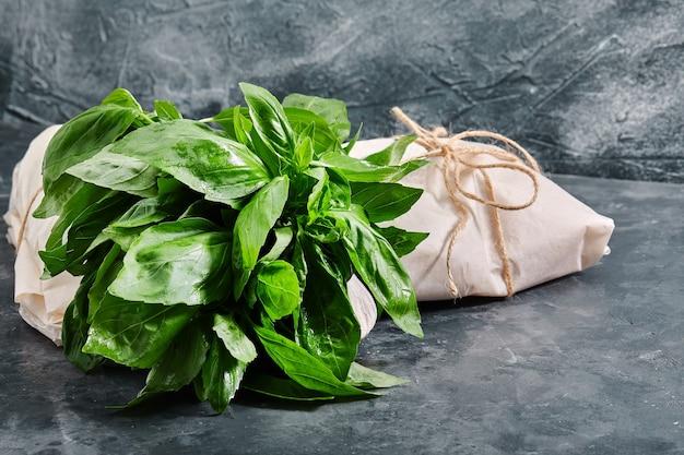 灰色のテーブルの上にある新鮮な緑のバジルの束、エコパッケージ食品の配達、環境問題。