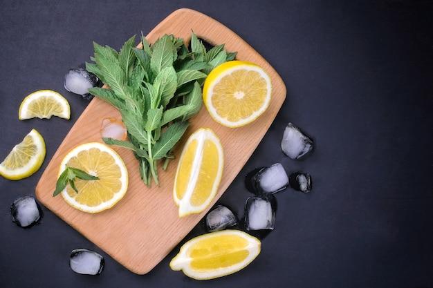 レモンスライスと角氷が付いている木の板の上の新鮮なミントの束は、黒い背景ではありません。上面図。