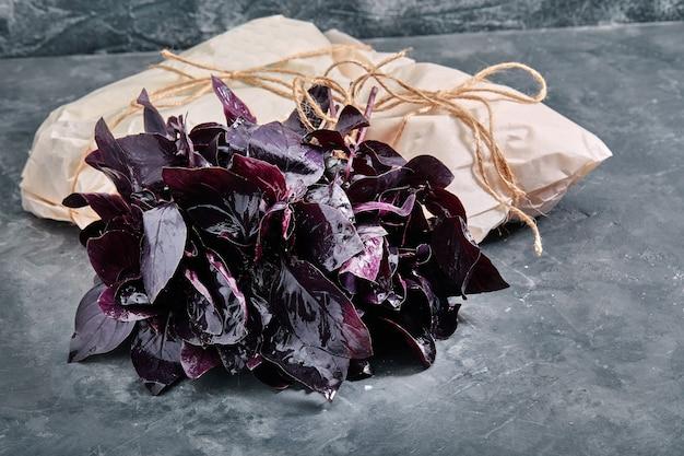 Букет из свежего фиолетового базилика, на сером фоне, эко-упаковка. доставка еды, забота об окружающей среде.
