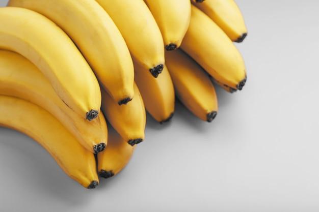 2021 년 유행 색상의 회색 배경에 신선한 노란색 바나나 한 무리.
