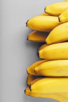 2021年のファッショナブルな色の灰色の背景に新鮮な黄色のバナナの束。