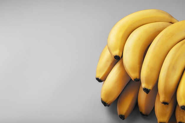 Букет свежих желтых бананов на сером фоне в модных тонах 2021 года.