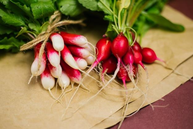 しわくちゃのクラフト紙に採れたての赤い大根の束。野菜を育て、収穫します。テキストのためのスペースと健康食品の背景。