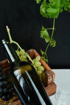 ブドウの房と白いテーブルの上のワインボトルをクローズアップします。高品質の写真