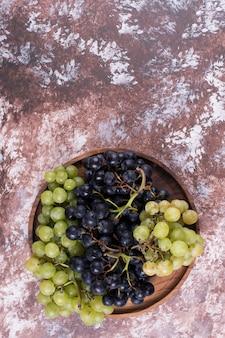 木製の大皿に緑と赤のブドウの房