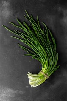 어두운 배경에 신선한 녹색 양파 또는 파 한 다발, 위쪽