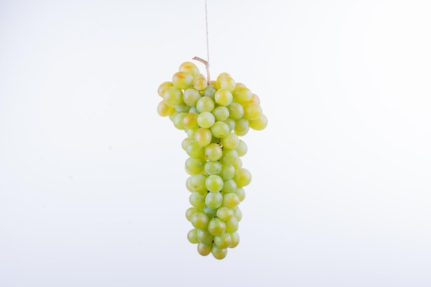 白いテーブルの上の緑のブドウの束。