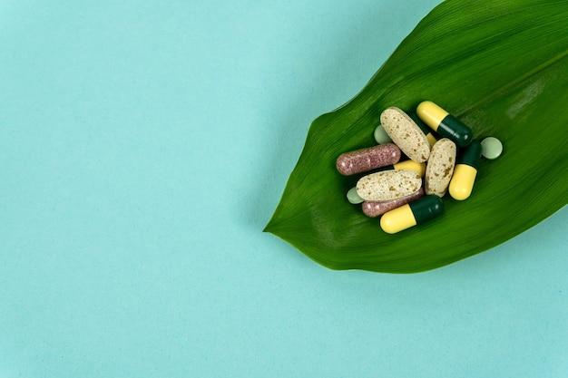 たくさんのハーブの丸薬がヤシの葉の上にあります代替治療に基づく自然医学