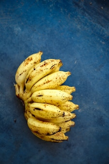 파란색 콘크리트 배경에 작은 익은 바나나 한 다발