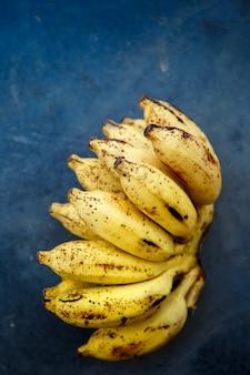 Связка маленьких спелых бананов на синем бетонном столе